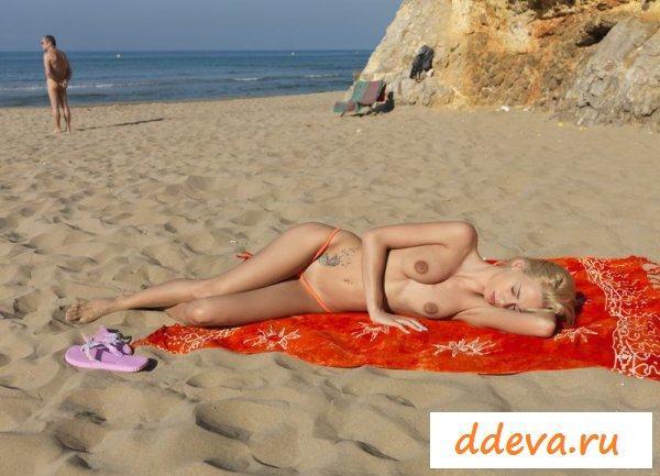 Нудистка загорает на пляже